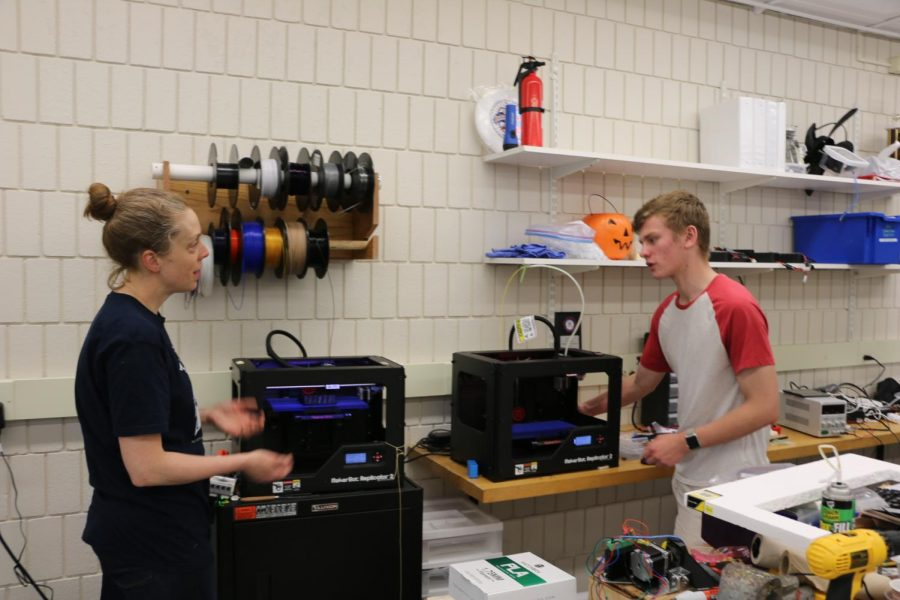 Director of Computer Science and Engineering Kate Lockwood teaching a student how to use the 3D printer.