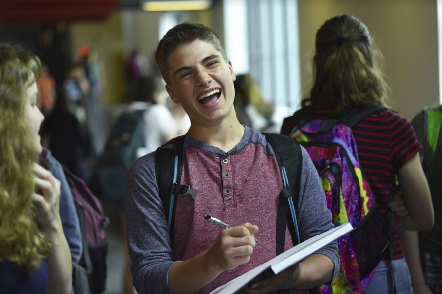 Ninth grader Jax Wittenberg laughs as he signs a yearbook.