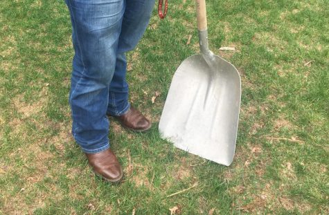 Tietel poses with a shovel and his boots; his farming essentials.