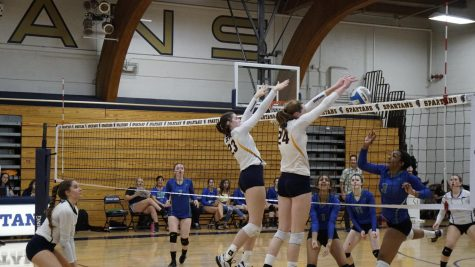 Junior Audrey Egly and junior and captain Kathleen Bishop block the ball against Blake on Sept. 14.