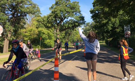 Students cheer on bikers biking along the Mississippi River at the Bike Classic.