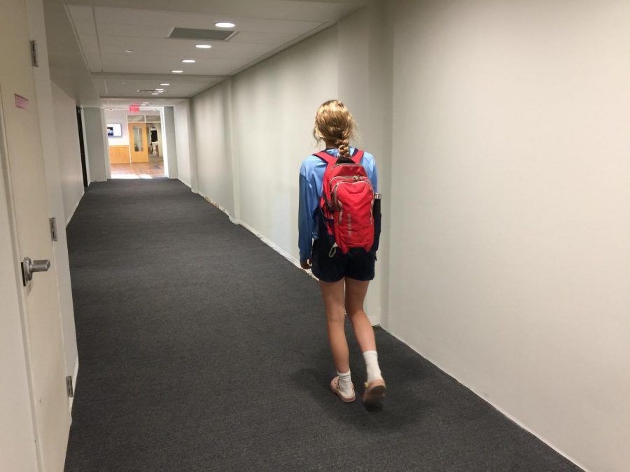 Senior+Muriel+Lang+carries+everything+she+needs+down+a+halway+formerly+filled+with+lockers.+