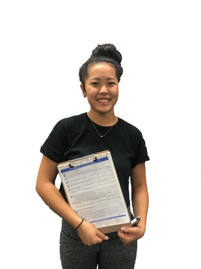 Senior Elea Besse holds voter registration papers.