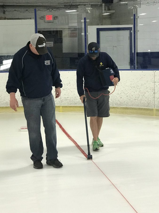 Edhlund (left) observes the painting of the ice rink.