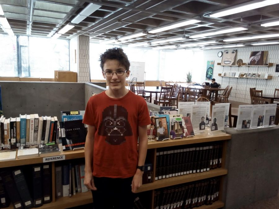 Sophomore+Raffi+Barocas+stands+in+front+of+the+library%27s+LGBTQ%2B+book+display.