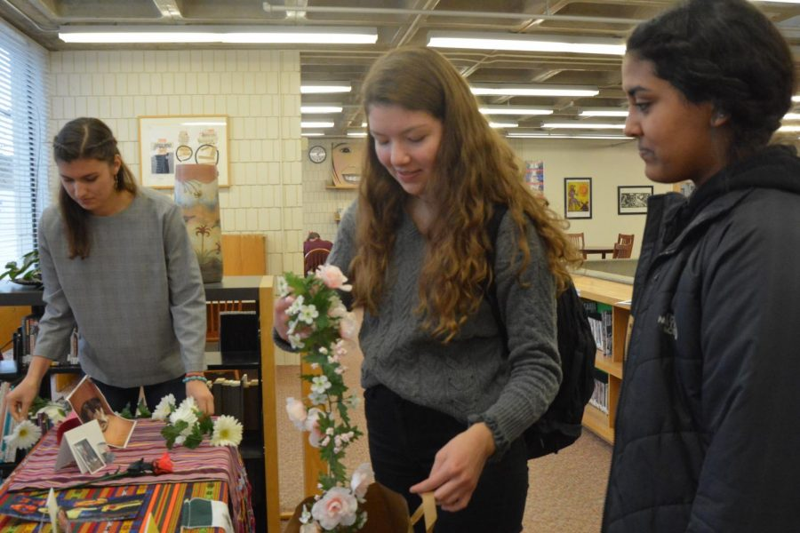 Senior Isabel Saavedra-Weis and Sophomores Pilar Saavedra-Weis and Aman Rahman put the final touches on the offrenda.