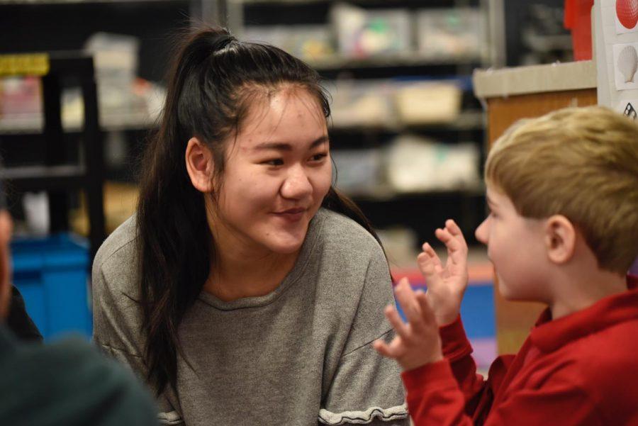 Senior Maya Orey chats with her kindergarten buddy.