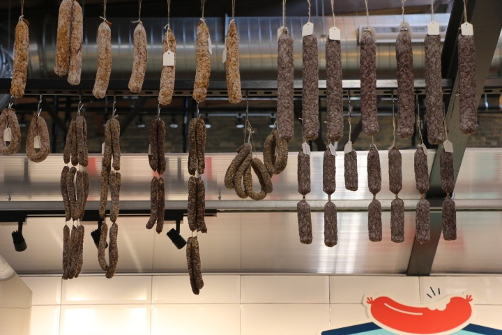 Dangling sausages hang above K'nack, a German-styled meat shop.