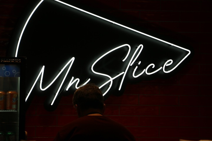 The sign at MN Slice, a pizza slice shop that serves unique square-square shaped pizza slices.
