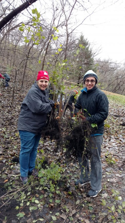 Advisor Mary Lincoln and PEP President Iris Shaker-Check holding the invasive buck thorn roots that plague Crosby Farm Park.