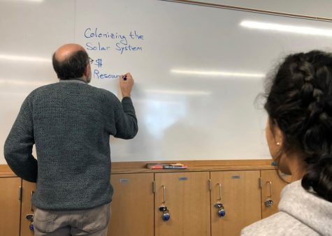 Upper School science teacher Dr. Heilig makes a list of the pros and cons to space colonization in the Space Science class.