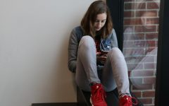 Junior Nina Smetana looks at her phone in the Schilling Center.