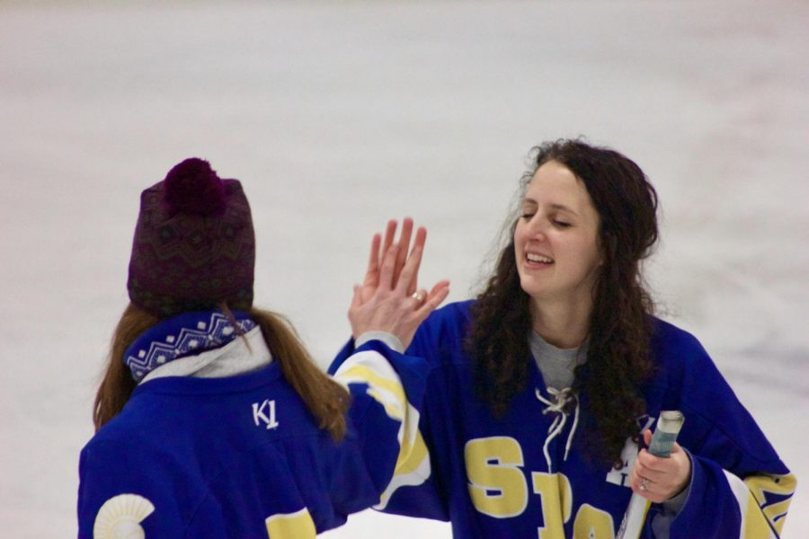 US Science teacher Christine Schwichtenberg high fives US Fitness teacher  Cari Jo Anderson after she played in the shoot the puck challenge.
