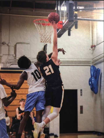 Senior Will Christakos rises to get a rebound.