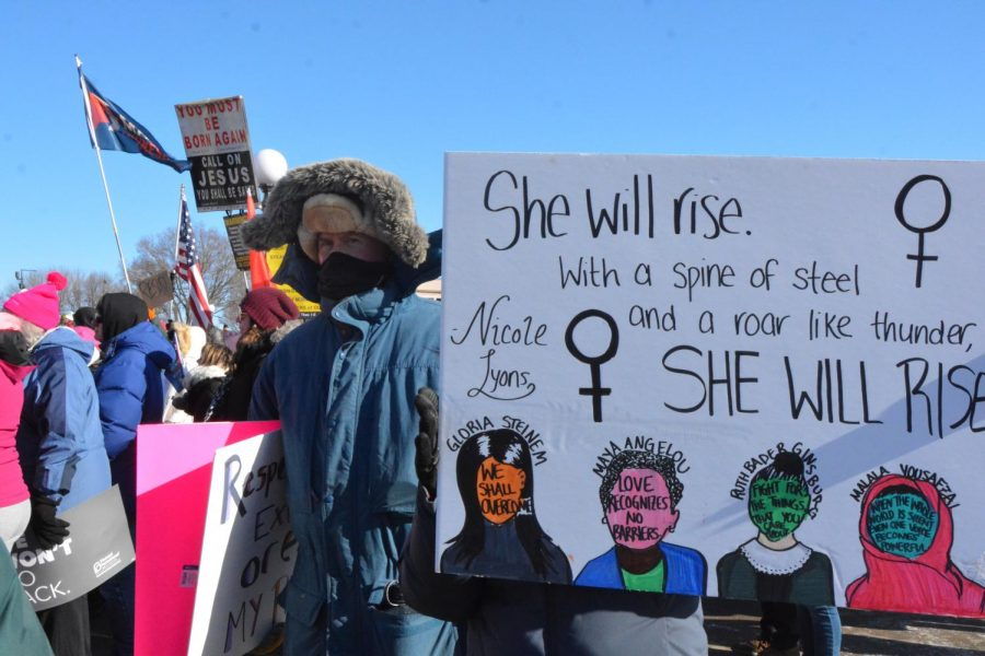 Marches hold signs and gather in front of the Minnesota State Capital to listen to speakers at the third annual Womens March.