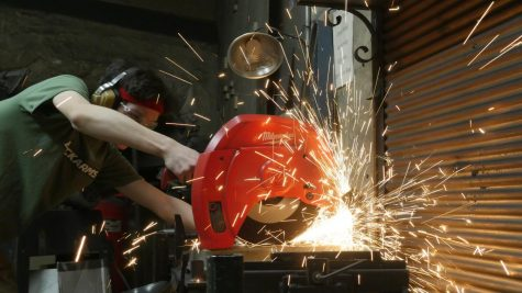 Senior Ben Atmore cuts the steel with a machine that produces sparks.