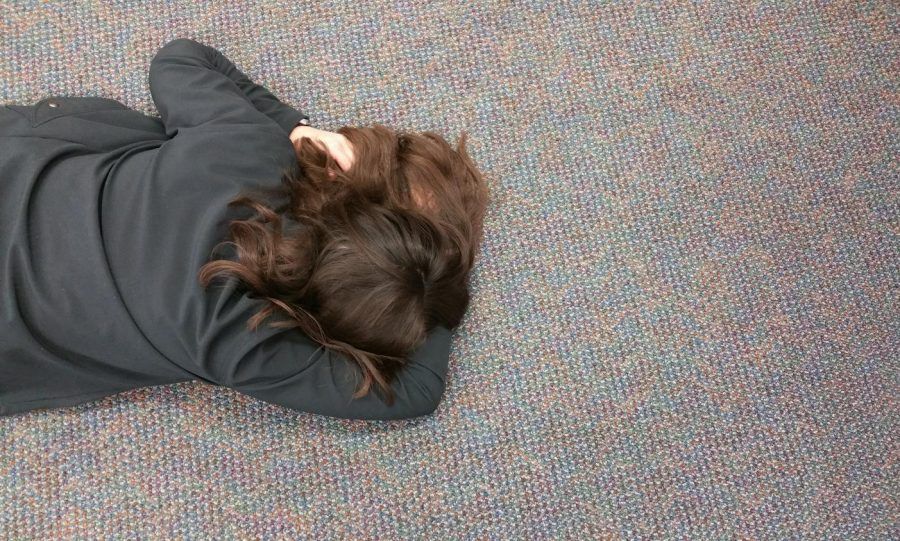 Senior Eliza Reedy naps on the floor of the Lower Library during the last Monday of her high school career.