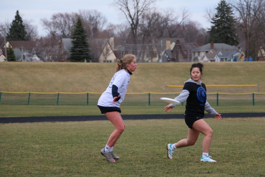 Senior and captain Elea Besse throws the frisbee to a teammate against Cretin.