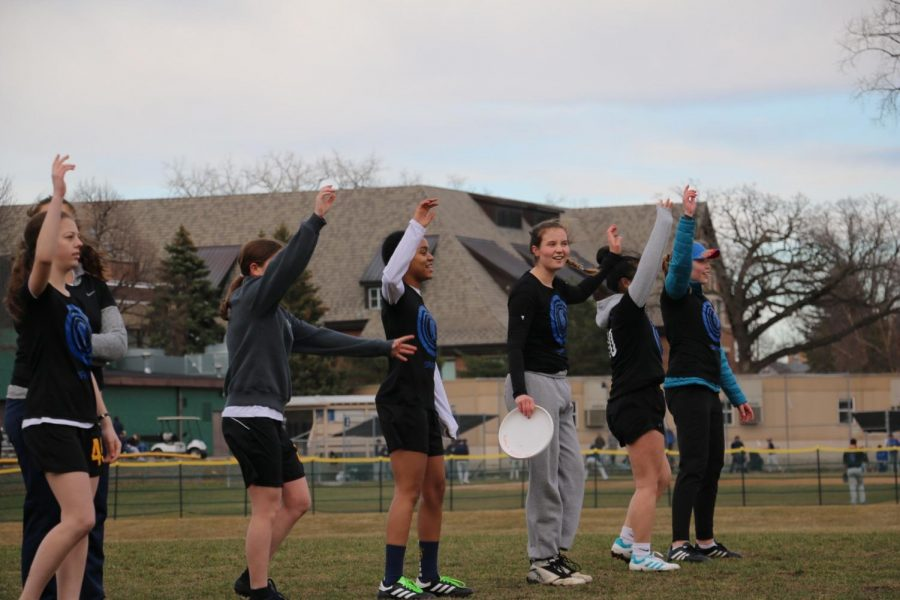 The Girls Ultimate Team raises their hands before pulling the frisbee for the play.