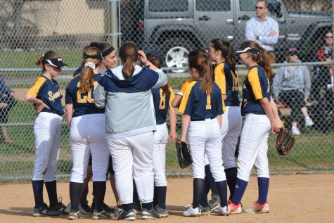The softball team huddles before their game begins.