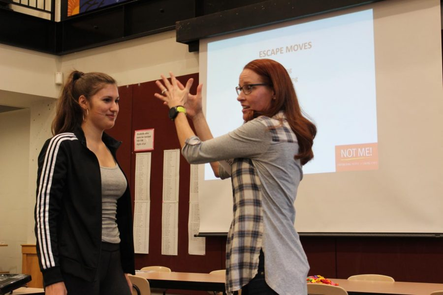 Senior Isabel Saavedra-Weis helps with an example during the self defense class.
