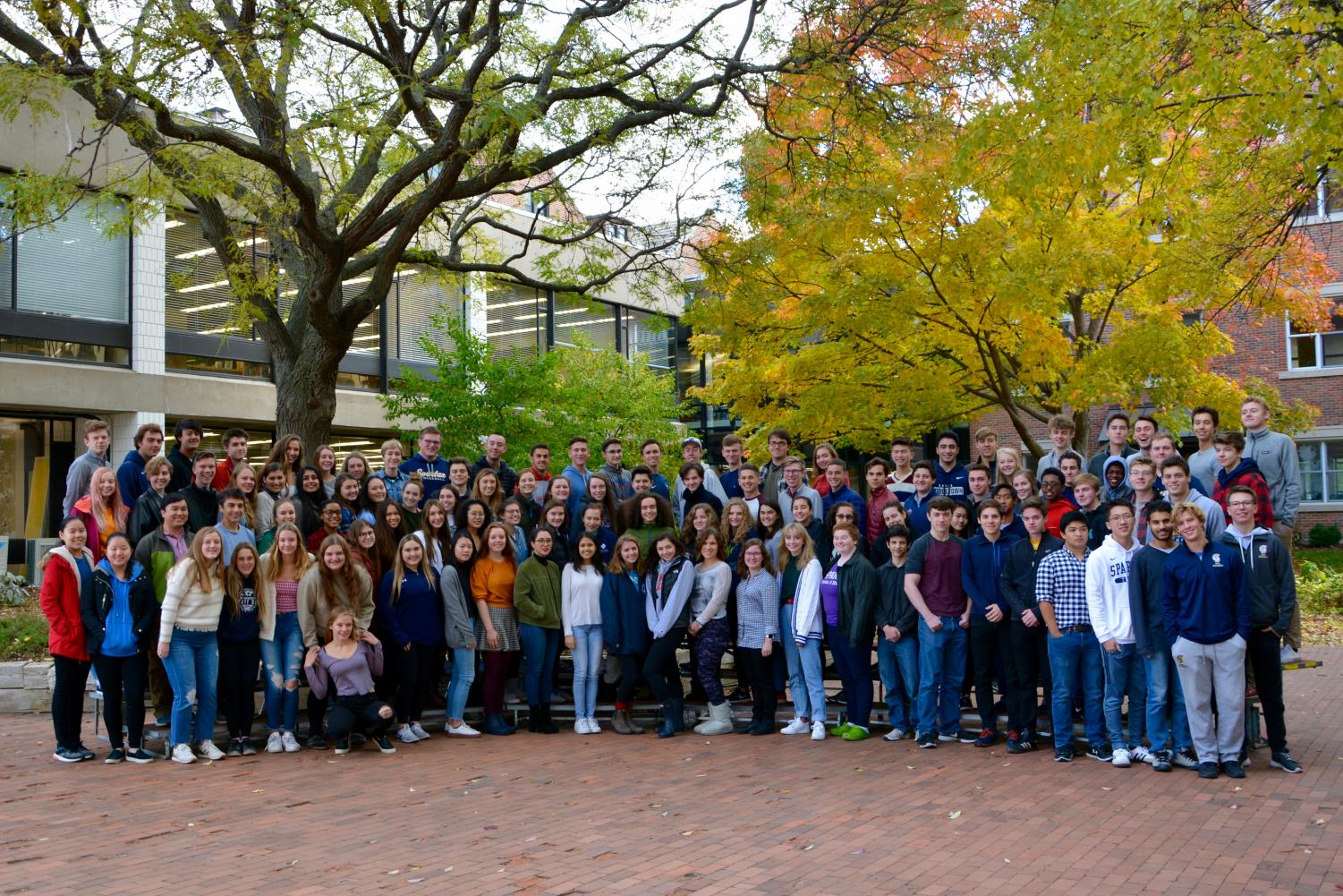 The Class of 2019 pose for a glass picture in the fall colors of Lilly Courtyard.