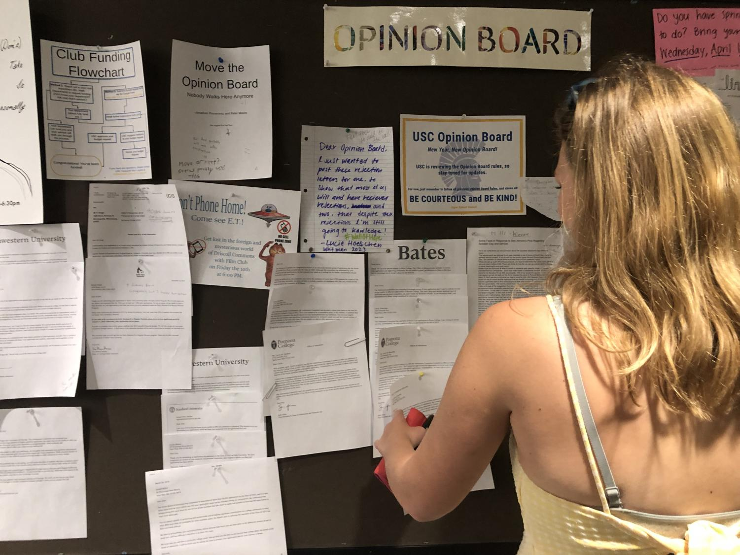 Junior Helen Bartlett reads the college denial letters posted on the opinion board.