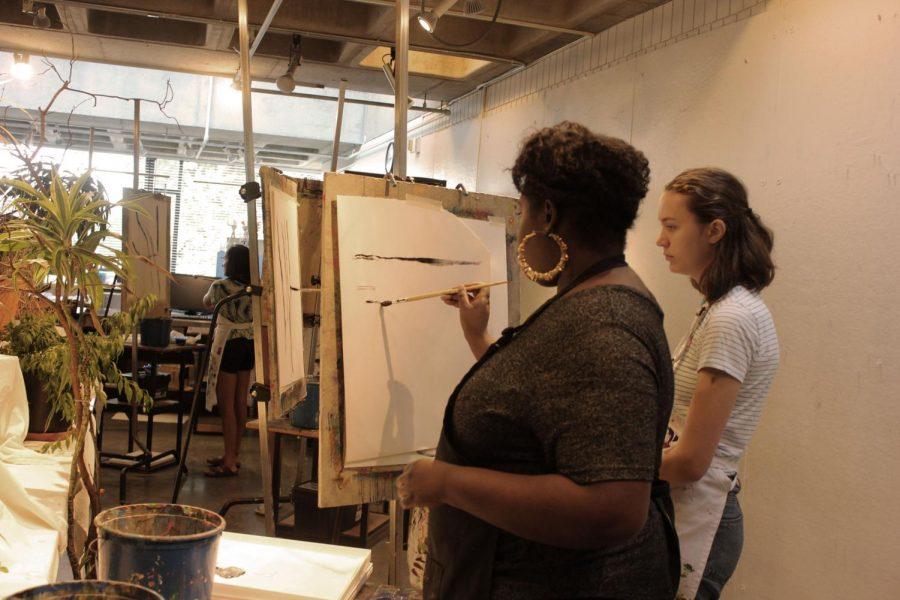 Upper School Art Teacher Mara Duvra shows a student a brushstroke.