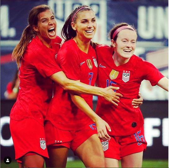 U.S. national players Tobin Heath, Alex Morgan and Rose Lavell celebrate a goal.