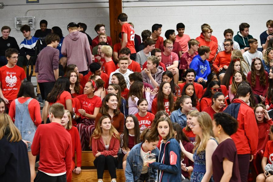 Juniors, wearing red, talk among one another as they wait for the assembly to commence.