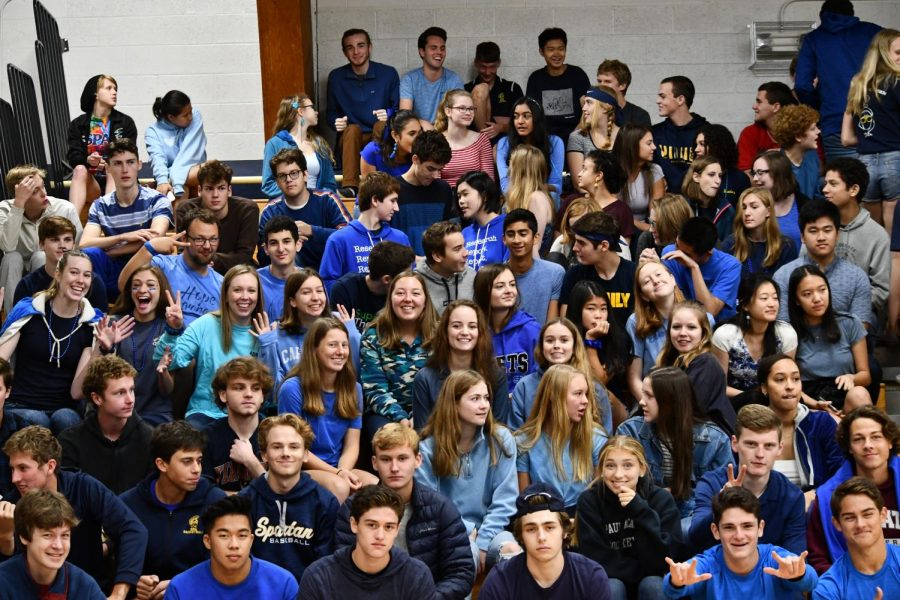 Seniors, wearing blue today, prepare for the kick off assembly, smiling.