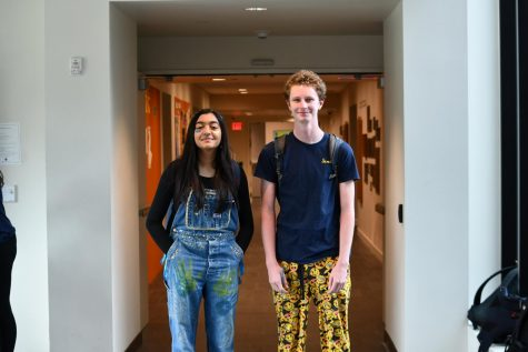 Seniors Ananya Narayan and Alex Herrmann decked out in blue and gold; Narayan wears her senior overalls while Herrmann wears gold, emoji-covered pants. Image from