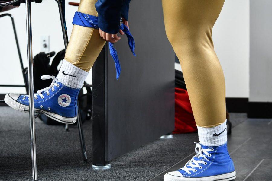 Junior Aman Rahman wore classic blue Converse with white socks; also wearing gold metallic leggings and a blue bandana tied around her leg.