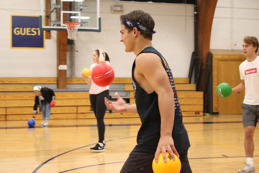 Senior Will Rathmanner tosses a ball in the air as he faces his opponents in the dodgeball tournament.
