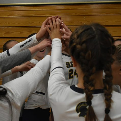 The Girls Varsity Volleyball team huddles before the start of the game.