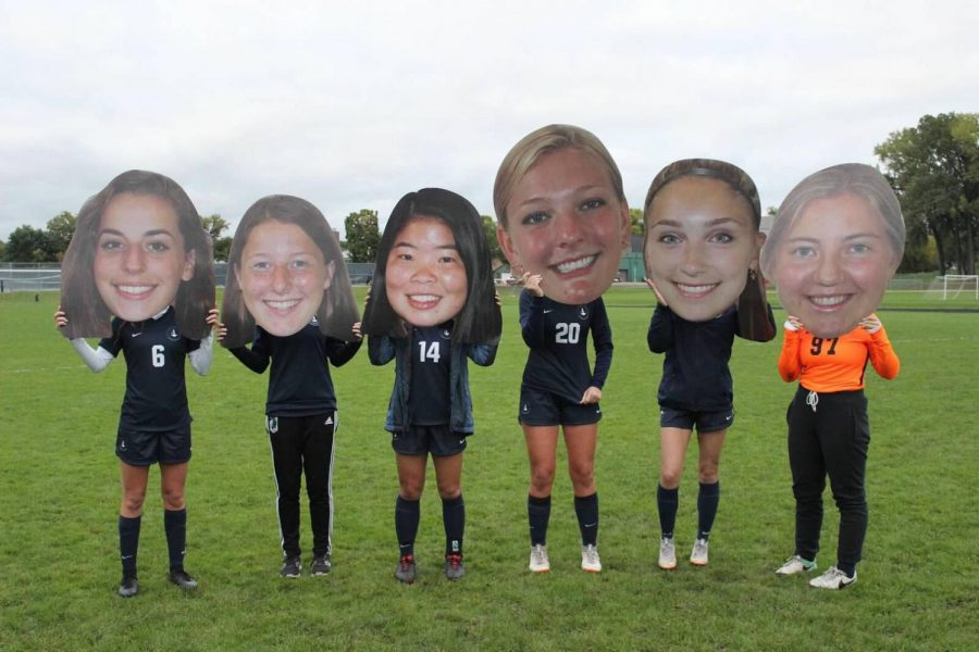 Seniors posed for a post-game picture with their cutouts, a team tradition.