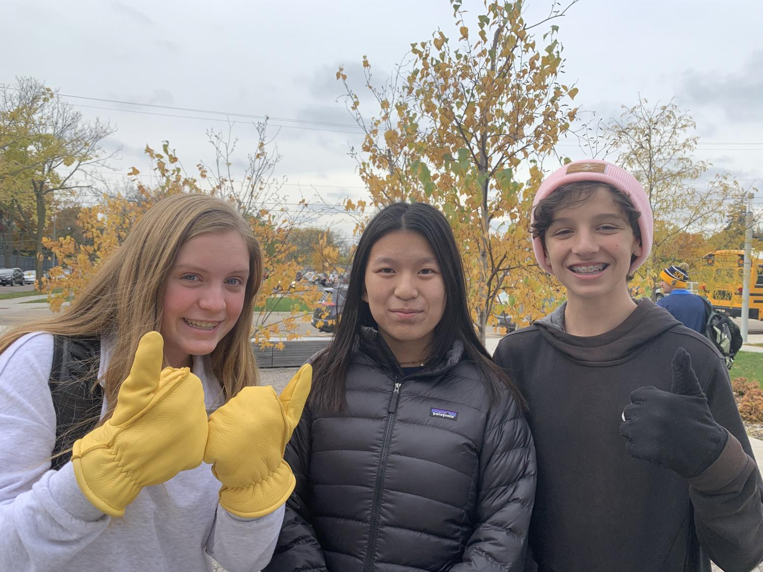 9th graders Greta Magnuson, Ivy Raya, and Aaron Lindeman stand outside of Huss Building in winter coats, hats, and gloves.