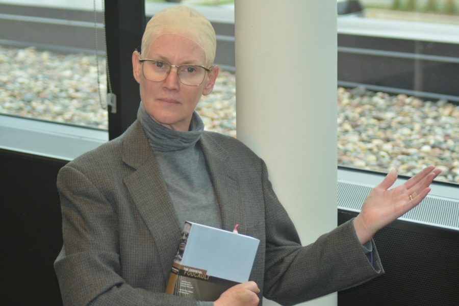 Upper school history teacher, Andrea Moerer, dressed up as famous French historian Michel Foucault. She poses for a photo carrying his book.