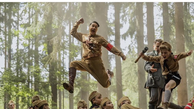 Director Taika Waititi who plays Jojo's imaginary friend jumps in the air with Jojo Rabbit (played by Roman Davis).