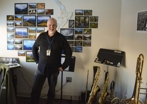 Randy Reid stands in his office, surrounded by many brass instruments.