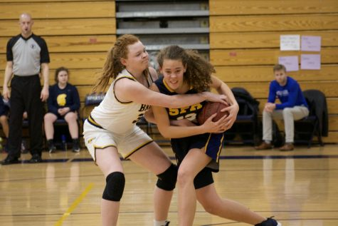 Junior Gabriella Thompson fighting for the ball against Breck