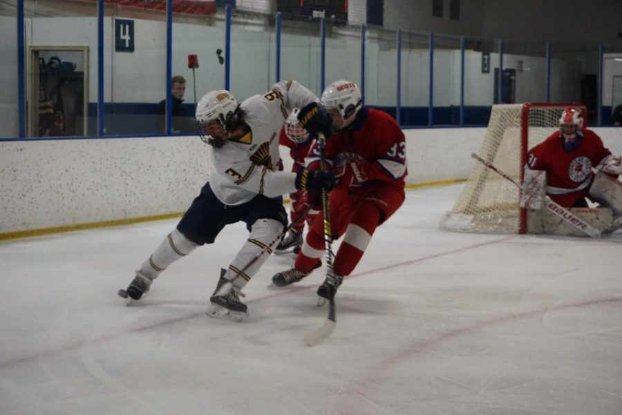 Ninth-grader+George+Peltier+blocks+a+Highland+player+from+grabbing+the+puck.+