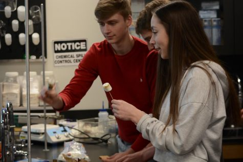 Juniors Adam Holod, Jonas Bray, and Julia Baron share a Bunsen burner.