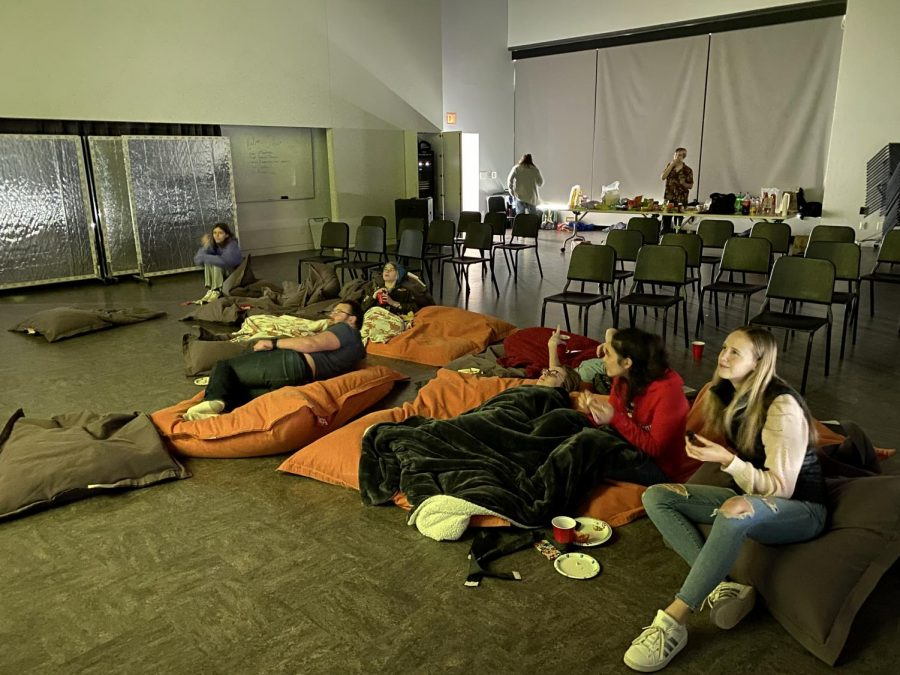 Students sit on pillows, eat snacks and watch one of the five movies included in the marathon.