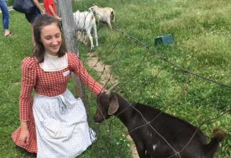 Sophomore Ruth Mellin pets a goat at Gibbs Farm in her period clothing.