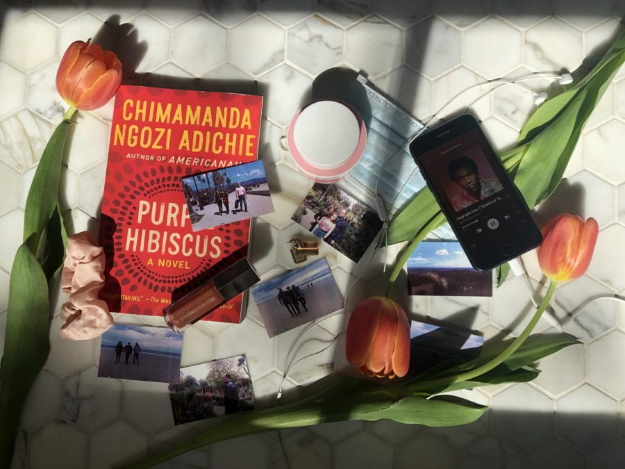 "My quarantine essentials include flowers, my blue face mask for the grocery store, Fenty lipgloss, my pink scrunchie, an overnight face mask, gold earrings, the book ""Purple Hibiscus"", my photos, earbuds, and my phone. My phone is playing the album ""Because the Internet"" by Childish Gambino, which I have been listening to a lot while at home. My earrings are my grandma's from the 70's and I just like to wear them around the house to feel put together. The photos are from my family's trip to LA. All of my items are in the sunlight which is also an essential because it makes me happy."