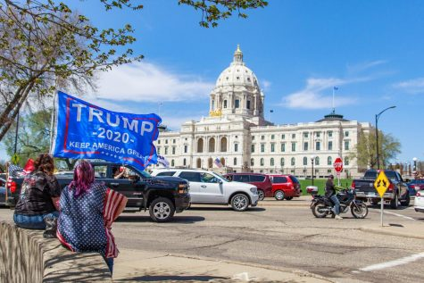 A protestor holds a pro-Trump flag as vehicles surround the Minnesota State Capitol in protest of Gov. Tim Walz's efforts to combat the coronavirus pandemic. May 2, 2020.