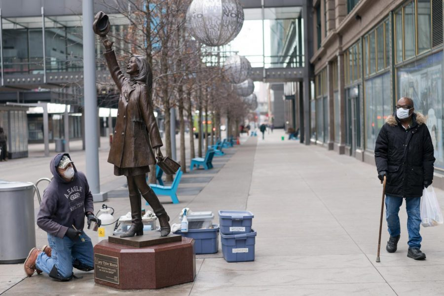 Two people wearing face masks, a worker cleaning the Mary Tyler Moore statue and someone passing by, glance at each other in Minneapolis, Minnesota.