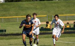 Senior Michael Bagnoli dribblings the soccer ball around defenders
