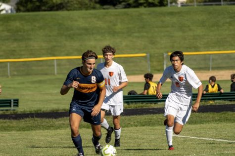 Senior Michael Bagnoli dribblings the soccer ball around defenders